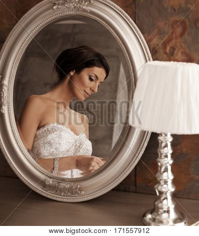 Beautiful bride in mirror, looking down.
