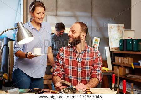 Young woman serving coffee to tinkering man in workshop.