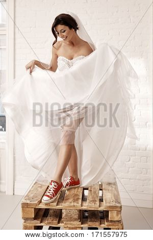 Provocative bride wearing red sneakers and wedding gown. Standing on pallet.