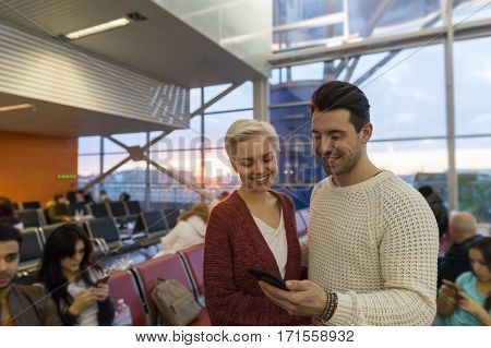 Young Couple In Airport Lounge Waiting Departure Happy Smile Man And Woman Use Cell Smart Phone, Flight Delay