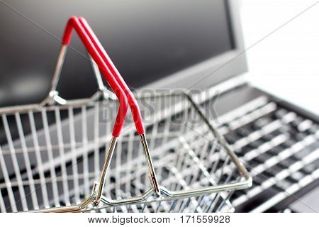 Shopping basket on laptop buying online abstract background concept