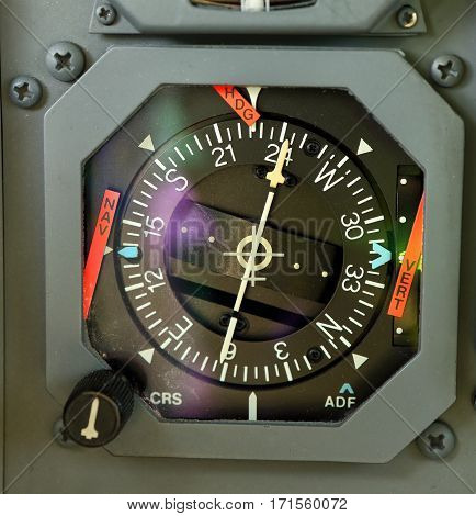 Gray rounded analog navigational display in aircraft cockpit