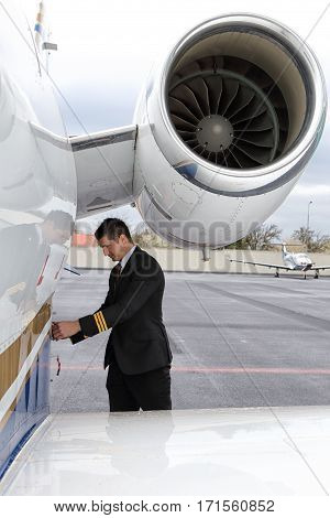 Young pilot locking baggage door of the small jet