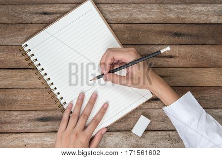 woman hands holding pencil and rubber eraser writting down on the book Top View with Copy Space on vintage background