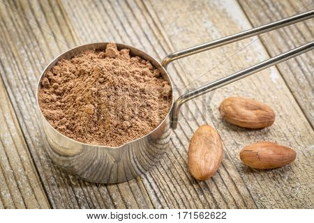 cacao powder in a metal measuring scoop against grunge wood background with some raw beans