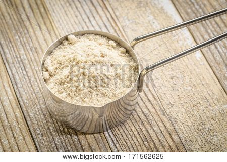 whey protein powder in a metal measuring scoop against grunge wood background