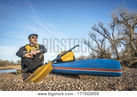 a senior male paddler is taking a rest on a gravelbar during stand up paddling on the South Platte RIver, cold season scenery