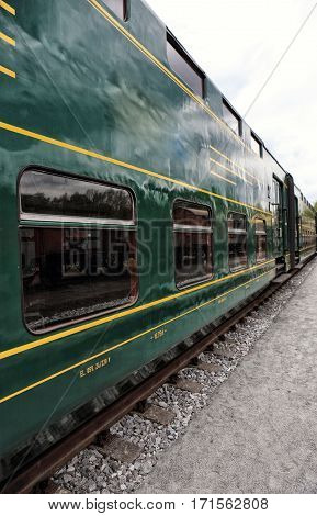 Green vintage railway double decker car with yellow lines