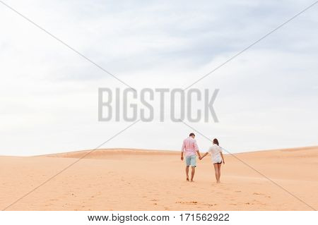 Young Man Woman Walking In Desert Couple Girl And Man Hold Hands Back Rear View Sand Dune Landscape Background
