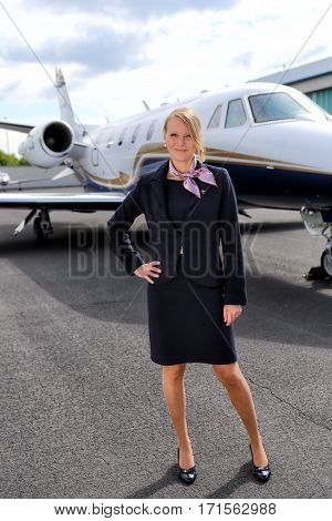Uniformed stewardess standing in front of business jet - portrait