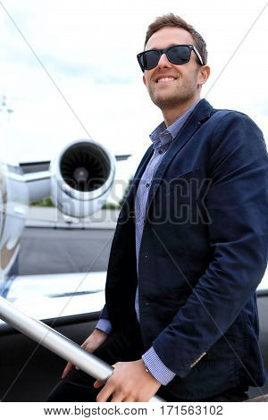 Young man embarking business jet with the engine in the background