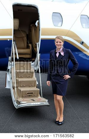 Young blonde flight attendant waiting for the passengers by the executive jet door
