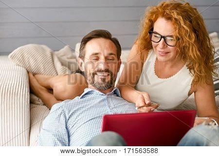 Full interesting ideas. Humorous smiling curious couple sitting at home and using the laptop while expressing positive emotions having conversation