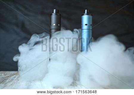 Electronic Cigaretts And A Cloud Of Steam On The Table. Mechanical Mod. Ends.