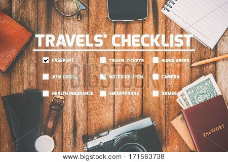 Travel Checklist for Preparing for a Trip mobile phone money passport camera pencil eyeglass book Watch in vintage color on wooden table Checklist.