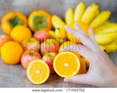 hand holding orange with fruits on background apples oranges banana plums