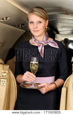 Young blonde flight attendant standing in the aisle with the glass of champagne