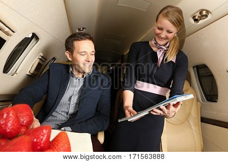 Young man in jet choosing the magazines offered by airhostess