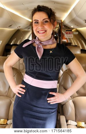 Smiling Airhostess of business jet standing in aisle