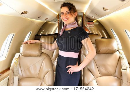 Flight attendant with the arm on the chair of the business jet