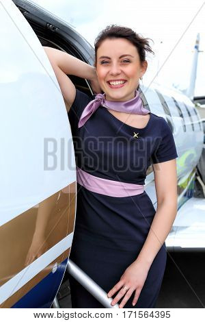 Brunette stewardess standing on the steps and doors of the jet plane