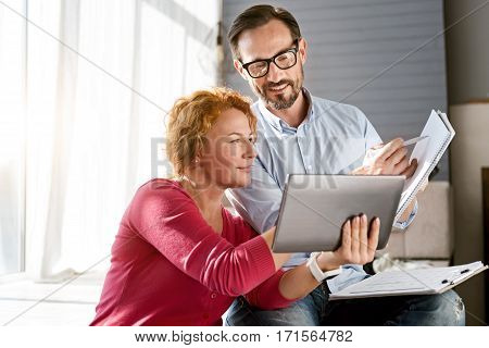 Creative family weekend. Positive smiling energetic middle aged couple sitting at home and using the tablet while expressing positivity and making notes