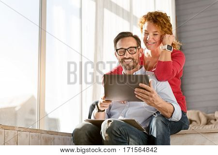 Listening to the music together. Cheerful smiling optimistic middle aged couple sitting at home and using the tablet while expressing positivity and listening to the music