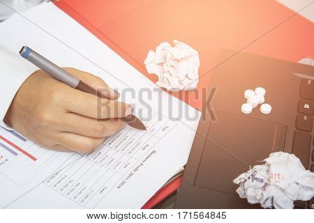 Close-up businesswoman working with drug put on laptop. migraine. business lazy concept.