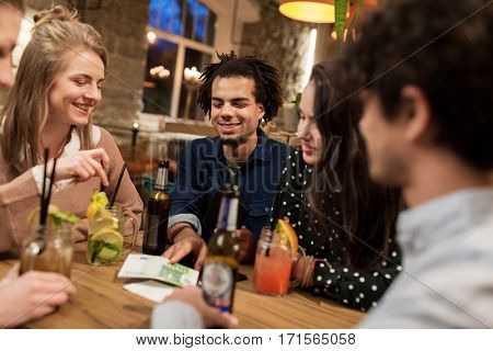 leisure, people and holidays concept - happy friends with drinks, money and bill at bar or cafe
