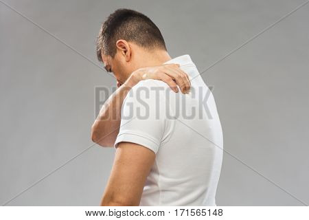 people, healthcare and problem concept - close up of man suffering from pain in upper back over gray background