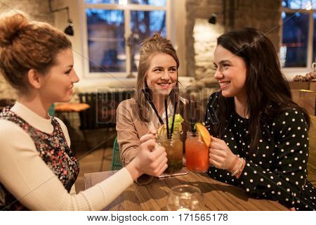 leisure, celebration, party, people and holidays concept - happy friends clinking drinks at restaurant