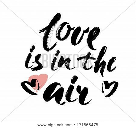 Love is in the air hand lettering. Hand drawn card design. Handmade calligraphy. Brush Lettering Design. Vector illustration