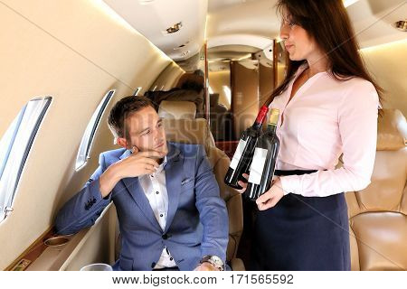 Young passenger of business jet choosing wine offered by stewardess