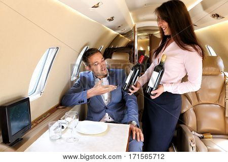 Young passenger of business jet choosing wine offered by airhostess