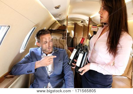 Young passenger of business jet choosing wine offered by flight attendant