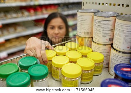shopping, consumerism and people concept - woman taking jar with food from shelf at grocery