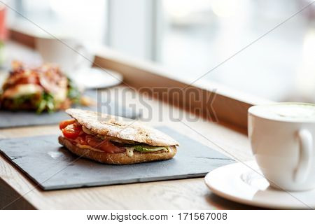 food, dinner and eating concept - salmon panini sandwich with tomatoes and cheese on stone plate at cafe or restaurant