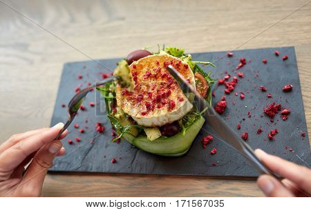 food, culinary, haute cuisine and people concept - woman eating goat cheese salad with vegetables and dried raspberries using fork and knife at restaurant or cafe