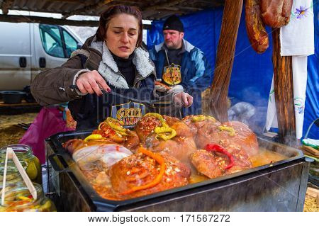Hecha Ukraine - February 11 2017: Cook one of the teams of butchers fry the pork foreshank on a baking sheet during the 11th International gastronomic festival of butchers in the village Hecha.