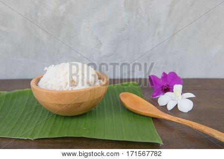 Cooked rice in bowl on green banana leaf spoon and orchid .