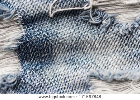 clothes, wear and fashion concept - close up ripped denim jeans with holes