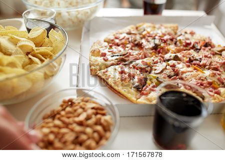 fast food and unhealthy eating concept - pizza, potato crisps and glass of cola drink on table
