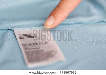 clothes, laundry, people and housekeeping concept - finger pointing to label with users manual on clothing item