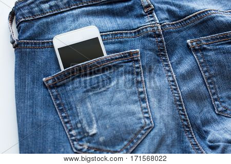 technology and communication concept - smartphone in pocket of denim pants or jeans