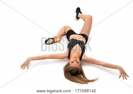 Pretty girl in black top and shorts lying on the floor studio shot from above
