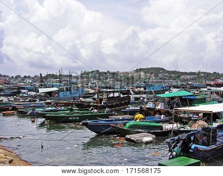 Cheung Chau, Hong Kong - March 22, 2003: Harbour of the island of Cheung Chau with many fishing boats. Fishermen work on their small boats. In the water floats a lot of garbage.