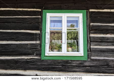 Closed window with the green frame on the timbered wall