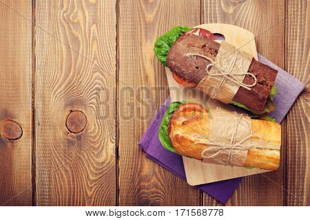 Two sandwiches with salad, ham, cheese and tomatoes on wooden table. Top view with copy space. Toned