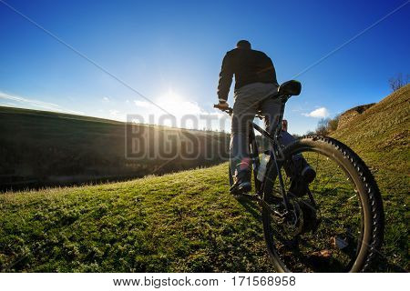 Young Cyclist riding on the Beautiful Meadow Trail on sunny day. Detail of the bicycle. Wheel. WIde angle. Travel in the countryside. Spring season.