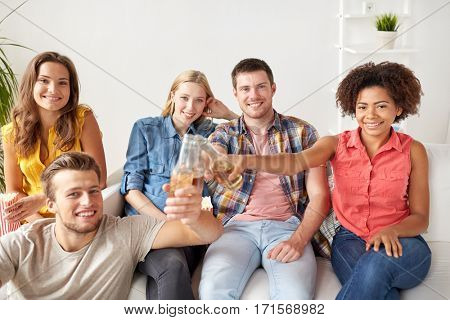 friendship, people and holidays concept - happy friends with popcorn drinking beer at home
